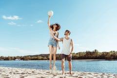 Aktiv man och kvinna som spelar volleyboll på stranden tillsammans Royaltyfria Bilder