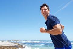 Aktiv man som kör tillfälligt på stranden royaltyfri bild