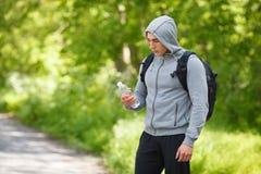 Aktiv man som rymmer en flaska av vatten som är utomhus- Den unga muskulösa mannen släcker törstat Royaltyfri Fotografi