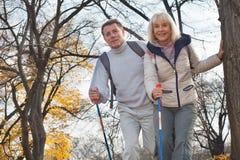Aktiv mitt åldrades par som utomhus fotvandrar royaltyfri bild