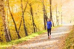 Aktiv och sportig kvinnalöpare i höstnatur Fotografering för Bildbyråer