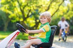 Aktiv pys som kör den pedal- bilen i sommarträdgård Arkivbilder