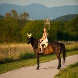 Aktiv ritt för ung kvinna en häst i natur Arkivfoto