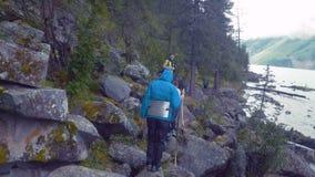 Aktiv som den mogna kvinnan klättrar, vaggar upp till överkanten av klippan som hoppar över sprickor Rundat vaggar med enorma ste lager videofilmer