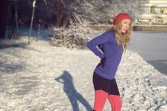 Aktiv ung kvinna med knip i henne tillbaka fotografering för bildbyråer