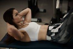 Aktiv ung kvinna som utarbetar hennes abs i idrottshall för konditionklubba Fotografering för Bildbyråer