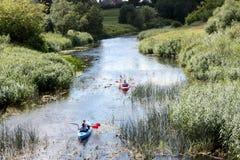 Aktiv vilar på floden Folket på kajaker seglar längs en vanlig liten flod Arkivfoton