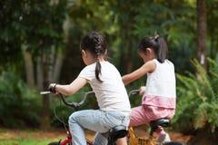 Aktiva asiatiska barn som rider den utomhus- cykeln fotografering för bildbyråer
