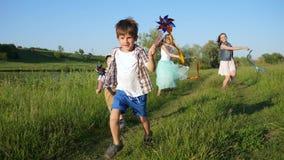 Aktiva barn med färgrika väderkvarnar och band i händer kör och skrattar på gräsmatta stock video