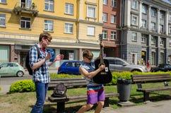 Aktiva buskers med gitarrer och klockastadsgatan arkivbild