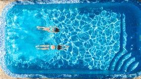 Aktiva flickor i sikt f?r surr f?r simbass?ngvatten flyg- fr?n ?ver, barn simmar, ungar har gyckel p? tropisk familjsemester arkivfoto