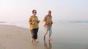 Aktiva höga par som kör på den sandiga stranden på soluppgång lager videofilmer