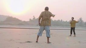 Aktiva höga par som spelar bollen för tai-chiballon på stranden lager videofilmer