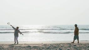 Aktiva höga par som spelar bollen för tai-chiballon på stranden i ultrarapid arkivfilmer