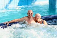 Aktiva höga par som tycker om bubbelpoolen Royaltyfria Foton