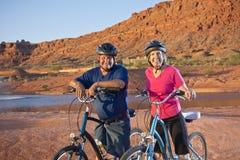 Aktiva höga par som tycker om en cykel, rider tillsammans Arkivfoto