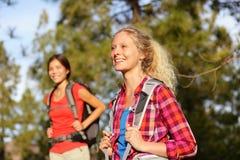 Aktiva kvinnor - fotvandra flickor som går i skog Arkivbilder
