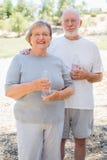 Aktiva lyckliga sunda höga par med vattenflaskor Arkivbilder