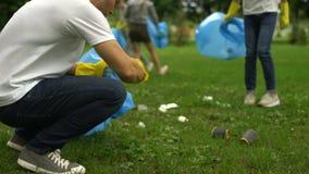 Aktiva medborgare som samlar avskräde parkerar offentligt, samhälle mot förorening arkivfilmer