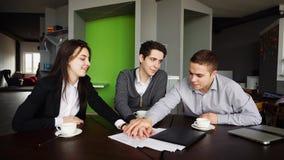 Aktiva och intelligenta kollegor, män och kvinnor arbetar tillsammans a royaltyfri bild