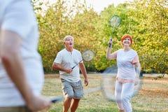Aktiva pensionärer som spelar badminton Arkivfoto