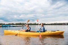 Aktiva turister som ror med skovlar som sitter i kanot arkivbild