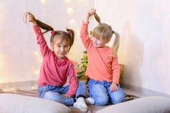 Aktiva unga barn av flickor skrattar och bedrar omkring och att sitta på Fotografering för Bildbyråer