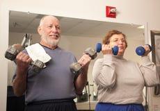 Aktiva vuxna par som utarbetar i idrottshallen Royaltyfria Foton