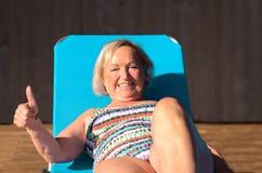 Aktive ältere blonde ein Sonnenbad nehmende Frau Stockfoto
