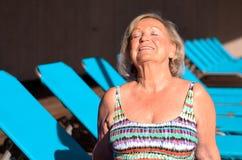 Aktive ältere blonde ein Sonnenbad nehmende Frau Lizenzfreie Stockbilder