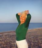 Aktive ältere Frau auf dem entspannenden Strand Stockfoto