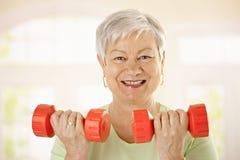 Aktive ältere Frau, die Übungen tut Stockbild