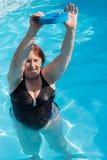 Aktive ältere Frau, die in einem Swimmingpool trainiert Stockbilder