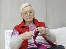 Aktive ältere Frau, die einen Schal strickt Lizenzfreies Stockbild