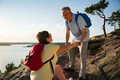 Aktive ältere Paare, die auf die Oberseite des Felsens wandern Lizenzfreies Stockbild