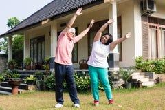 Aktive ältere Paare, die draußen mit den angehobenen Armen trainieren Lizenzfreie Stockbilder