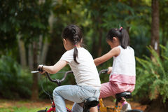 Aktive asiatische Kinder, die Fahrrad im Freien fahren stockbild