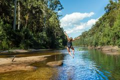 Aktive australische Frau, die in Fluss Fern-bushland springt lizenzfreie stockbilder