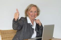 Aktive blonde ältere Frau, die sich Daumen zeigt Stockfotos