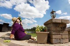 Aktive Dame im Ruhestand, die eine Pause von der Gartenarbeit macht Stockbild