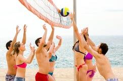 Aktive Erwachsene, die beachvolley spielen Stockfotos
