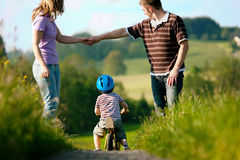 Aktive Familie am Sommer gehend und radfahrend Stockbilder