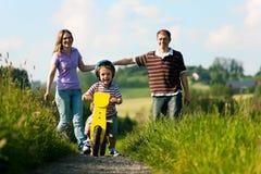 Aktive Familie am Sommer gehend und radfahrend Lizenzfreie Stockbilder