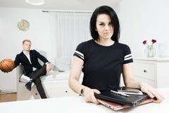 Aktive Frau beendete Arbeit am Schreibtisch und an elegantem Mann, die in den Hintergrund warten stockfotografie