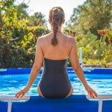 Aktive Frau, die im blauen Badeanzug auf Swimmingpool sitzt Lizenzfreie Stockfotos