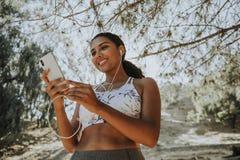 Aktive Frau, die Musik durch Kopfhörer hört Stockfoto