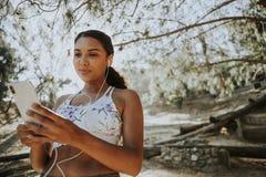 Aktive Frau, die Musik durch Kopfhörer hört Lizenzfreie Stockbilder