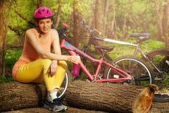 Aktive Frau, die nach dem Radfahren des Sitzens auf Klotz sich entspannt Lizenzfreies Stockbild