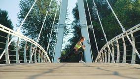 Aktive Frau, die in Stadtpark auf Steg trainiert und ausdehnt stock footage