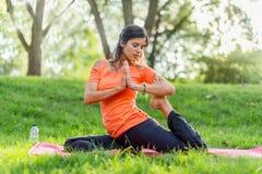 Aktive Frau, die Yogahaltungen bei Sonnenuntergang tut Lizenzfreies Stockbild